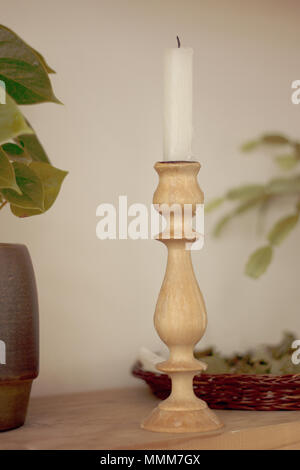 Long white candle in a wooden candlestick on the shelf - Stock Photo