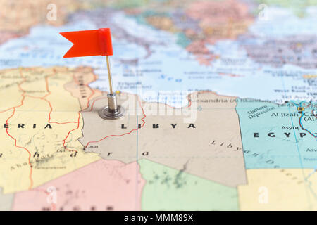 Small red flag marking the African country of  Libya on a world map. - Stock Photo