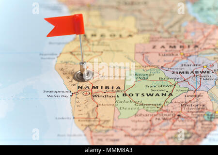 Small red flag marking the African country of  Namibia on a world map. - Stock Photo