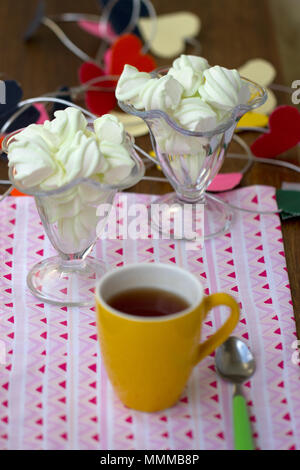 Tea in yellow cup with candy for breakfast - Stock Photo