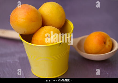 Apricots in a small yellow bucket on purple table - Stock Photo
