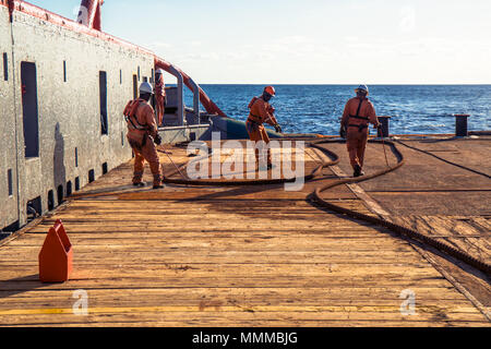 Anchor-handling Tug Supply AHTS vessel crew preparing vessel for static tow tanker lifting. Ocean tug job. 3 AB and Bosun on deck. They pull towing wi - Stock Photo