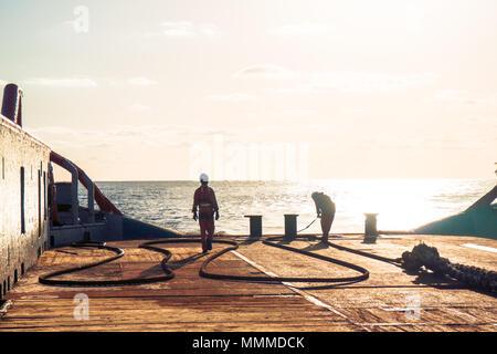 Anchor-handling Tug Supply AHTS vessel crew preparing vessel for static tow tanker lifting. Ocean tug job. - Stock Photo