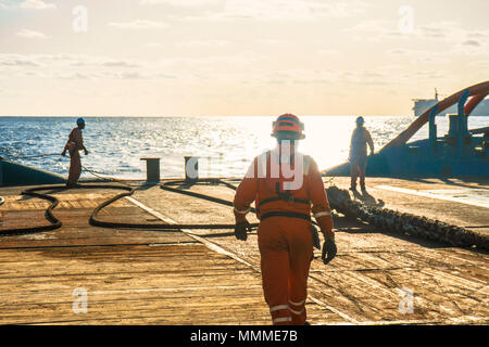 Anchor-handling Tug Supply AHTS vessel crew preparing vessel for static tow tanker lifting. Ocean tug job. 3 AB and Bosun on deck. Good teamwork - Stock Photo