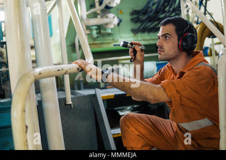 Marine engineer inspecting ship's engine with torchlight in engine control room ECR. Seamen's work. - Stock Photo