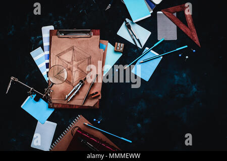 Draftsman or designer workplace with craft paper, sketches, compasses, rulers, clipboards and pencils on a dark stone background. Top view with copy s - Stock Photo