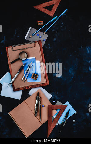 Clipboard with craft paper and sketches on a designer workplace. Sketches, compasses, rulers, clipboards and pencils in an architect or interior desig - Stock Photo