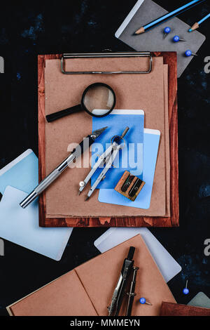 Wooden clipboard with craft paper and sketches on a designer workplace close-up. Sketches, compasses, rulers and pencils in an architect or interior d - Stock Photo