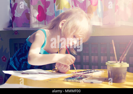 Beautiful baby girl painting with finger paints and with paint brush - Stock Photo