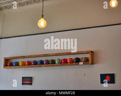 A row of brightly coloured Teapots for Sale on a rustic wooden shelf in the Red Kite Cafe in Edinburgh, Scotland. - Stock Photo