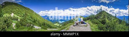 Wanderer auf der Bank bei Gipfelrast am Herzogstand - Stock Photo