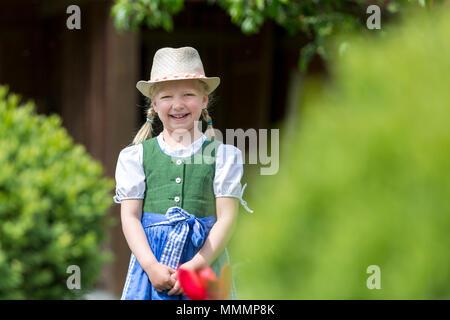 Portrait hübsches blondes Mädchen mit Dirndl im Garten