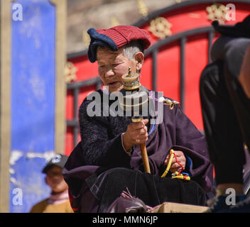 Tibetan pilgrim spins a prayer wheel outside the holy Bakong Scripture Printing Press Monastery in Dege, Sichuan, China - Stock Photo