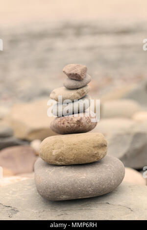 Pile of stones on a pebble beach in warm evening light. Calm peaceful zen concept - Stock Photo