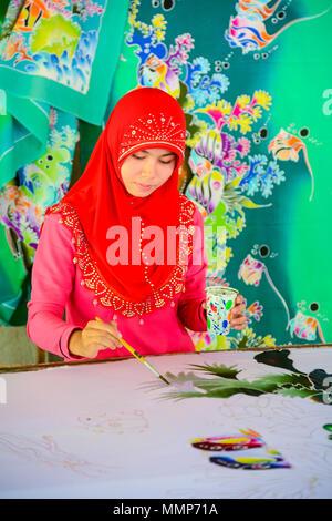 Krabi, Thailand - May 2, 2015: Beautiful Muslim woman wearing red hijab painting pattern on Batik fabric in Krabi, Thailand - Stock Photo