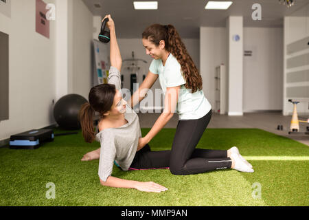Physical therapist assisting young caucasian woman with exercise with dumbbell during rehabilitation in the gym at hospital. Female physiotherapist tr - Stock Photo