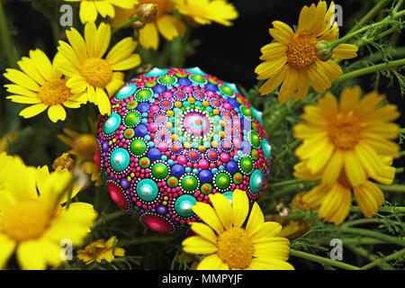 Beautiful hand painted mandala stone with yellow flowers - Stock Photo
