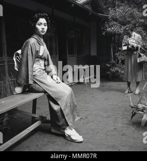 1950s, historical, attractive young adult female sitting on a bench outside wearing the traditional japanese clothing or costume, the kimono and being photographed by a western lady. The kimono is a silk garment that is wrapped around the body, tied with a wide belt, an obi and is the national attire for Japan. - Stock Photo