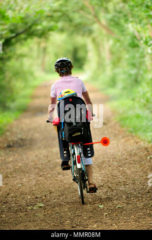 a woman riding  bicycle along  cycle path or heavily wooden country lane with a small child in a childrens seat on the pillion or back. cycling safety - Stock Photo