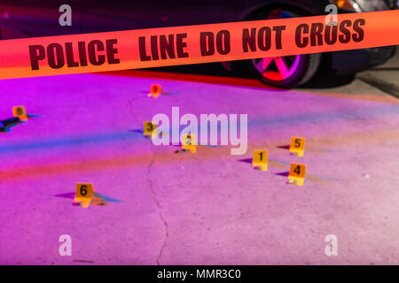 Cordon tape, marking a police line, is stretched in front of a crime scene. - Stock Photo