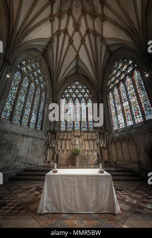 Light from the stained glass windows illuminates the  Alter table in the Lady Chapel at Wells Cathedral. - Stock Photo