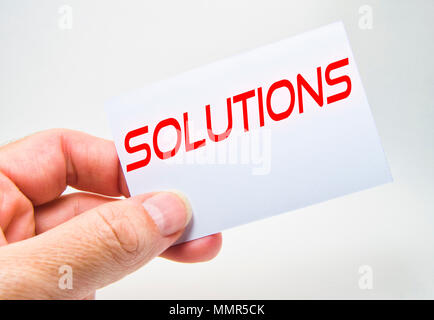 man hand holding a gray billboard with solution word written in it on a gray background - Stock Photo