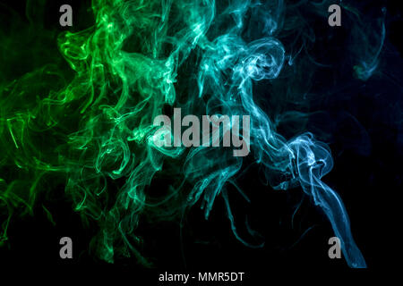 Colorful green and blue smoke  on a black isolated background. Background from the smoke of vape - Stock Photo