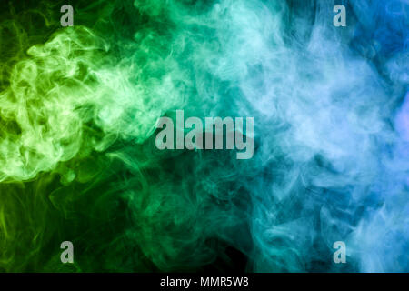 Colorful yellow, blue and green smoke  on a black isolated background. Background from the smoke of vape - Stock Photo