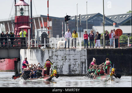 People watch teams taking part in the Gloucester annual Dragon Boat Regatta, where around 30 teams battle it out and race across the historic docks in 40-foot dragon boats. - Stock Photo