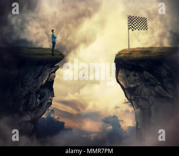 Business problem as a young man stand on a cliff need to go the other side to reach the finish flag. Overcome problems, successful planning and goal a - Stock Photo