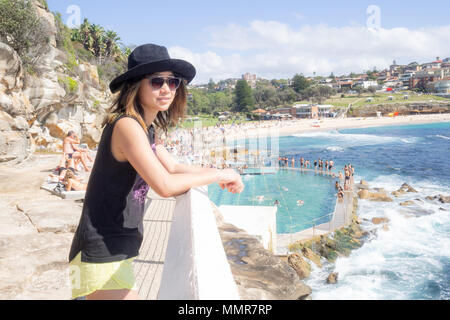 Young woman with hat and sunglasses walking by the public swimming pool at Bronte beach in Sydney Australia - Stock Photo