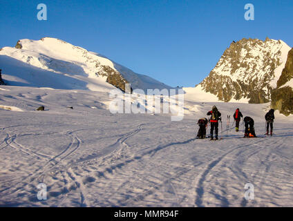 many backcountry skiers get ready to climb a high alpine peak in the Alps near Zermatt just after sunrise - Stock Photo