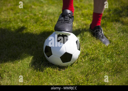 A footballer's boot and sock on top of a black and white leather football - Stock Photo