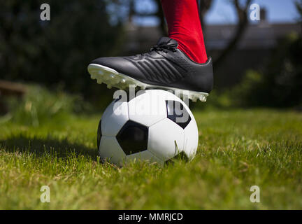 A football player's leg with sock and boot over a black and white leather football - Stock Photo