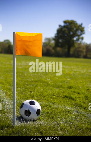 A corner flag post and leather football in the corner lines - Stock Photo