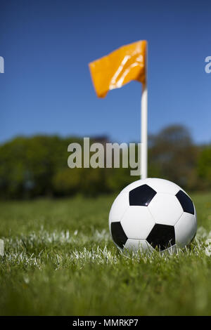 A corner flag post and leather football - Stock Photo