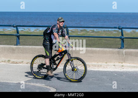 Southport, Merseyside, UK 13/05/2018. UK Weather. Bright colours on a bright sunny day at the coast, as temperatures in the North West are expected to rise.  Residents of the resort take light morning exercise on the seafront promenade at the start of the day. Credit: MediaWorldImages/AlamyLiveNews - Stock Photo
