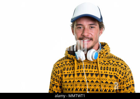 Studio shot of young happy man smiling while wearing cap and hea - Stock Photo