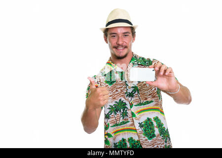 Studio shot of young happy tourist man smiling while taking pict - Stock Photo