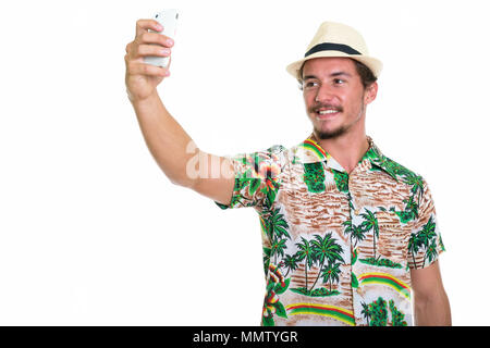 Studio shot of young happy tourist man smiling while taking self - Stock Photo