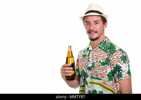Studio shot of young happy tourist man smiling while holding bot - Stock Photo