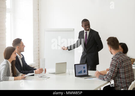 Smiling african-american coach in suit discussing business prese - Stock Photo