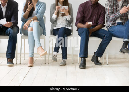 Diverse black and white people using smartphones tablets in queu - Stock Photo
