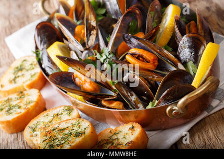 Cooked mussels with lemon, parsley and garlic macro in a saucepan on a table. horizontal - Stock Photo