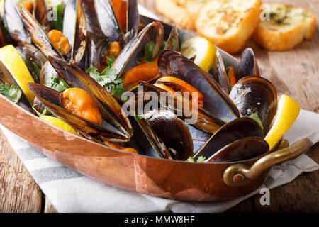Mussels with lemon and garlic macro in a saucepan on a table. horizontal - Stock Photo