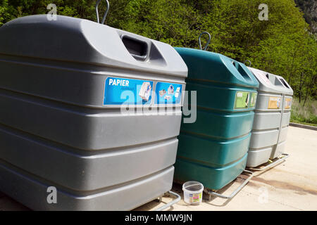 Large coloured recycling bins for glass paper and packaging Recycling bins in a row, lined up, Ariege, France, - Stock Photo