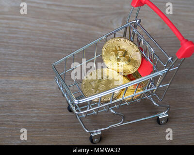 Golden bitcoin cryptocurrency in red shopping cart on desk wood background. Digital money cryptocurrency concept. - Stock Photo