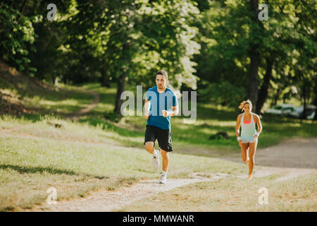 Young couple running in the park on the sunny day - Stock Photo