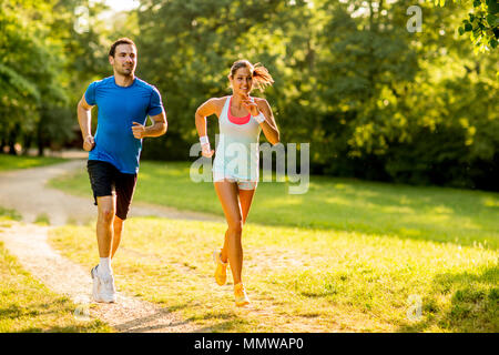Young couple running outdoors in the park on a sunny day - Stock Photo