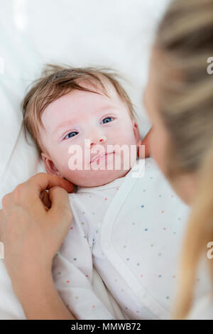beautiful blond mother, woman massages her baby - Stock Photo